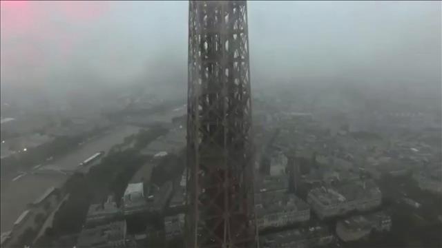Deux hommes escaladent la tour Eiffel à mains nues