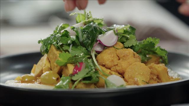 Salade d'herbes et dressage du plat de tajine de tofu aux olives et au citron confit