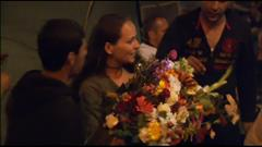 Une femme distribue des fleurs à des migrants